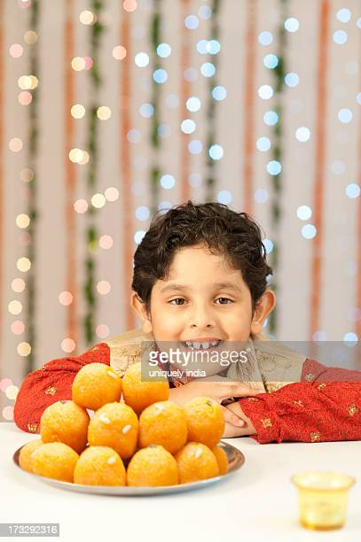 boy smiling and a plate of laddoo on diwali - diwali sweets stock photos and pictures