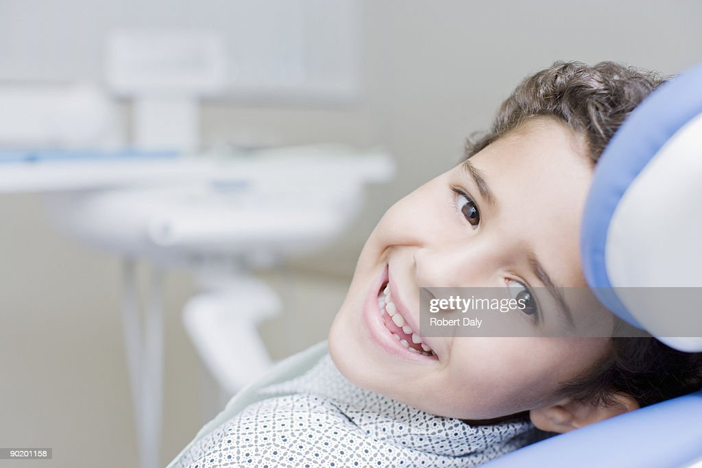 Boy smiling and sitting in dentists chair : Stock Photo