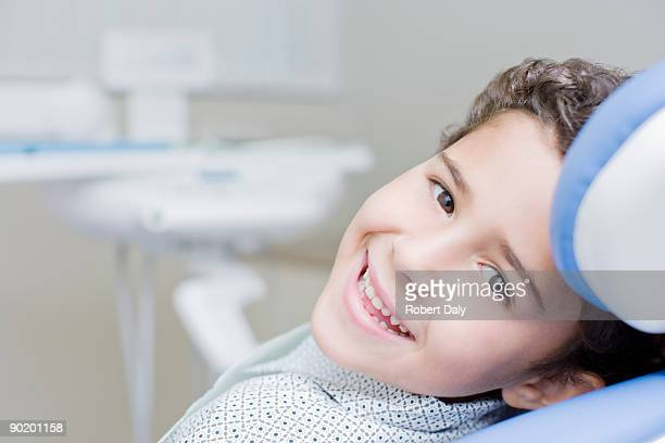 boy smiling and sitting in dentists chair - dental equipment stock pictures, royalty-free photos & images