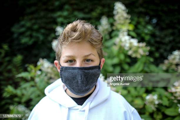 boy smiling behind face mask - angela auclair stock pictures, royalty-free photos & images