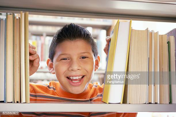 Boy smiling between books
