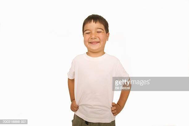 Boy (4-6) smiling, hands on hips, eyes closed
