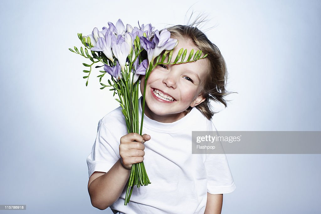Boy smiling holding bunch of flowers : Stock Photo