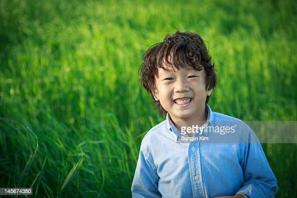 boy smiling in field - sungjin kim stock pictures, royalty-free photos & images