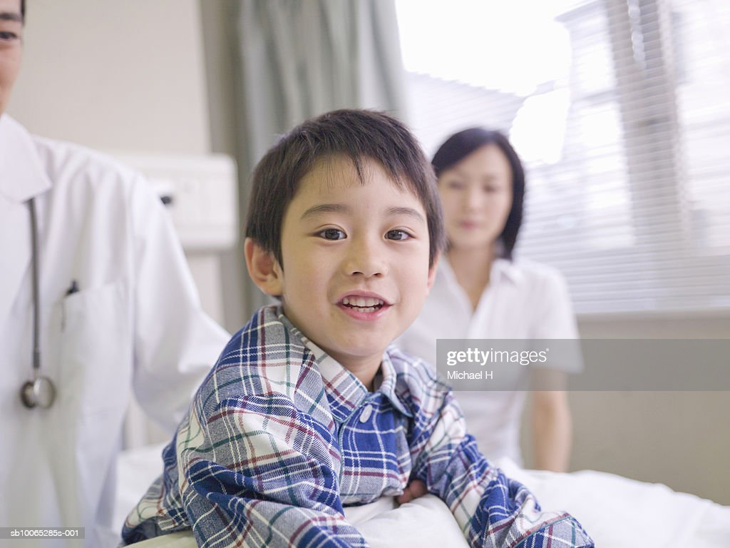 Boy (5-6) smiling in hospital bed, portrait : Foto stock