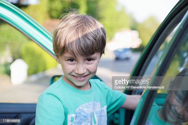 Boy smiling next to car