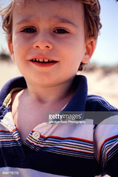 boy smiling on beach - carolyn ross stock pictures, royalty-free photos & images
