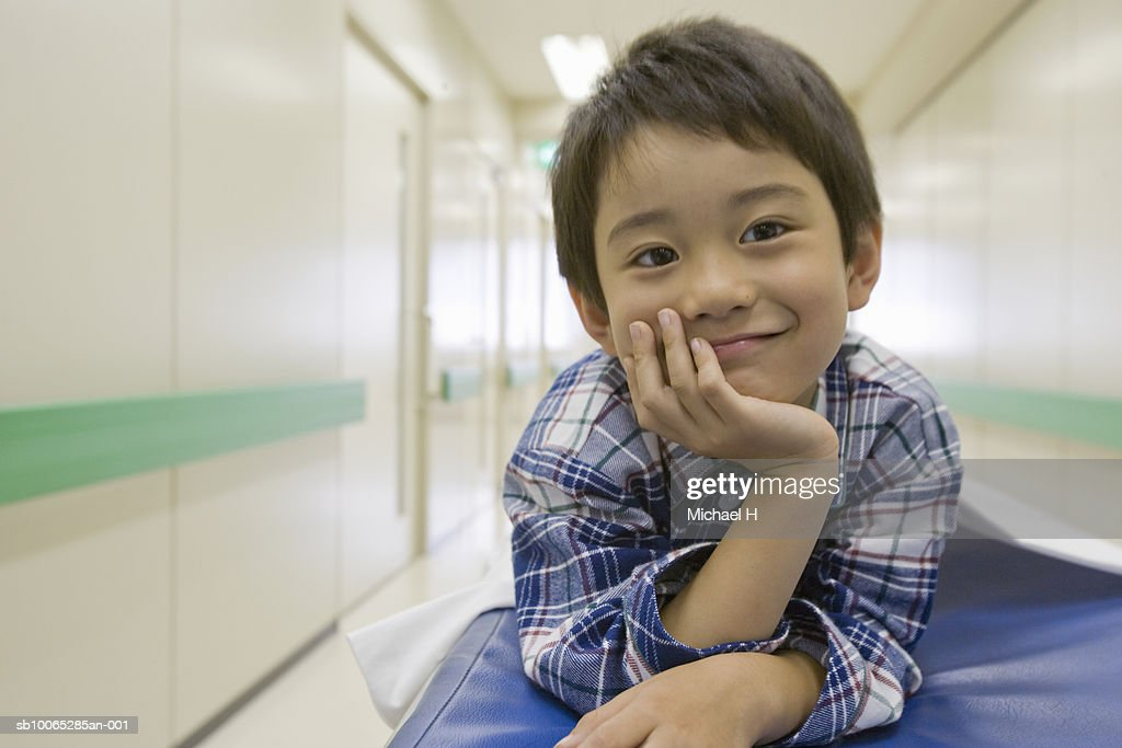 Boy (5-6) smiling on bed in hospital, portrait : Foto stock