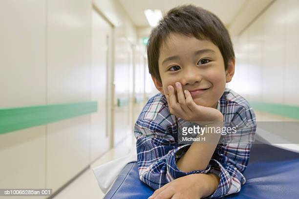 boy (5-6) smiling on bed in hospital, portrait - hand on chin stock pictures, royalty-free photos & images