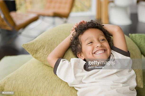 Boy smiling on couch.
