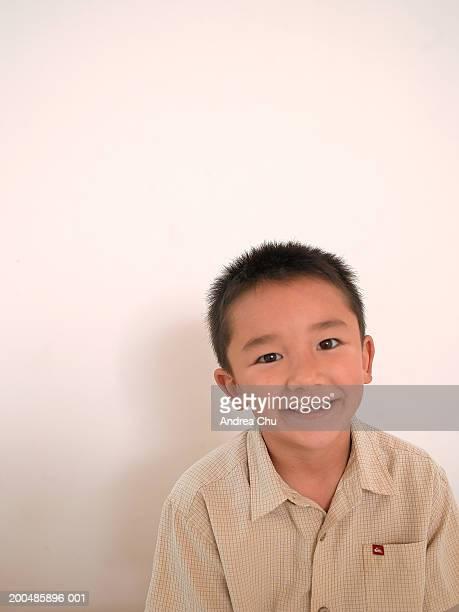 Boy (5-7) smiling, portrait