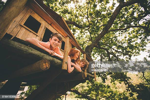 Boy smiling while playing with friends in a wooden treehouse