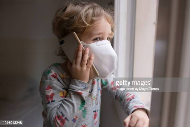 boy smiling while talking on the phone wearing a surgical mask - funny surgical masks stock pictures, royalty-free photos & images