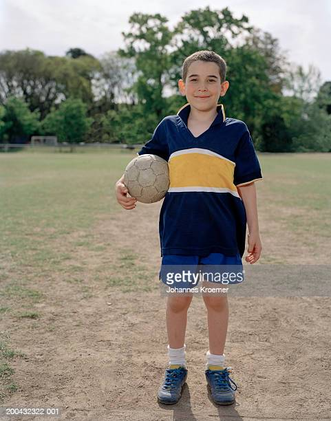 Boy (6-8) smiling with soccer ball on field, portrait