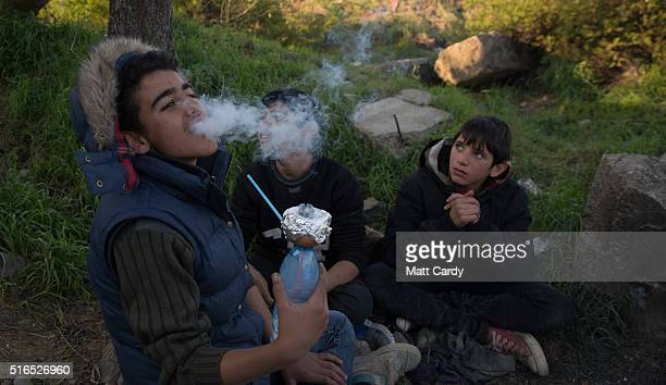A boy smokes a homemade shisha pipe at the Idomeni refugee camp on the Greek Macedonia border on March 19 2016 in Idomeni Greece Thousands of...