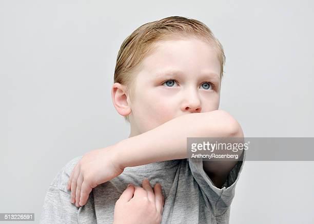 Junge Niesen in seinem Ellenbogen