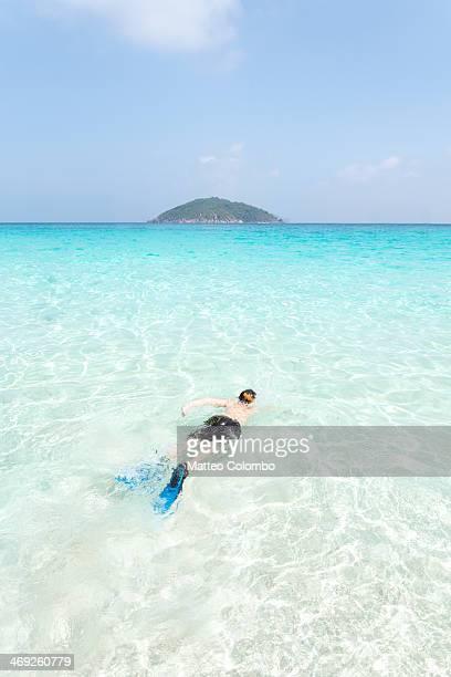 Boy snorkeling in crystal clear tropical sea