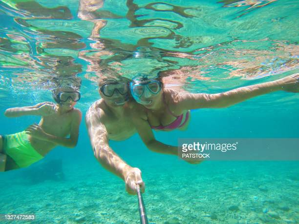 boy snorkeling with his parents in adriatic sea by the dugi otok island in croatia. - sea swimming stock pictures, royalty-free photos & images