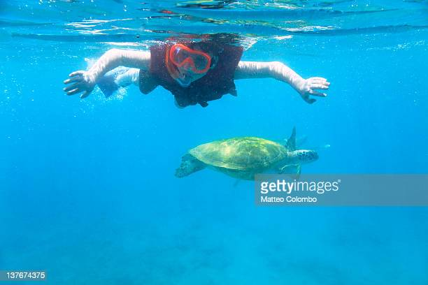Boy snorkeling with sea turtle