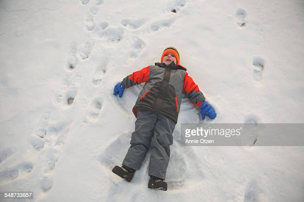 boy snow angel - snow boot stock photos and pictures