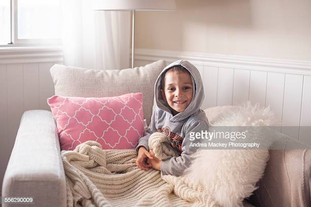 Boy snuggled up on lounge