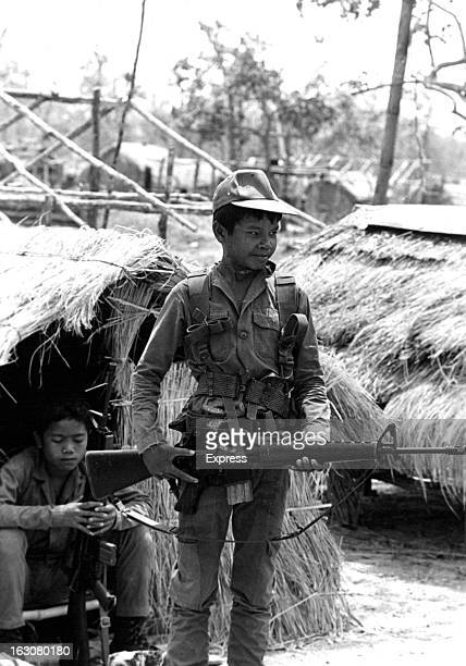 A boy soldiers at the forward outpost at Kalong holds a weapon in Laos 1955