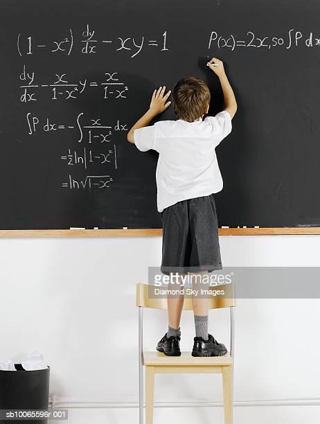 Boy (6-7) solving formula in classroom, rear view
