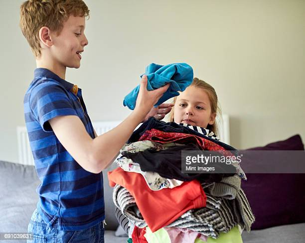 a boy sorting laundry and piling it up in the arms of a young girl. - chores stock pictures, royalty-free photos & images