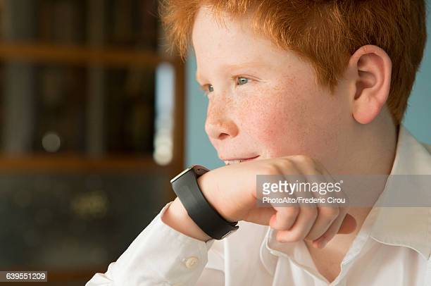 boy speaking into smartwatch - wrist watch stock pictures, royalty-free photos & images