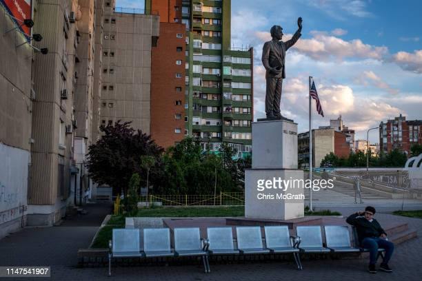 Boy speaks on the phone underneath a 10-foot-high statue of former U.S President Bill Clinton on Bill Clinton Boulevard on May 3, 2019 in Pristina,...