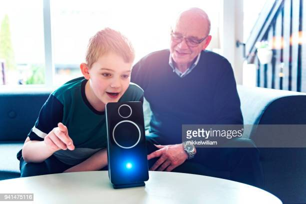 boy speaks to digital assistant while his grandfather look at him - assistant stock pictures, royalty-free photos & images