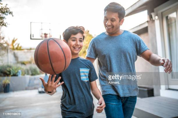 boy spinning basketball while walking by father - genitori foto e immagini stock