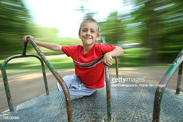Boy spinning on playground merry-go-round