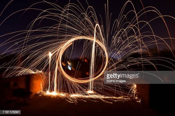 Boy spins a burning steel wool with a sling performing light painting during the New Year celebrations in Rajpura town.