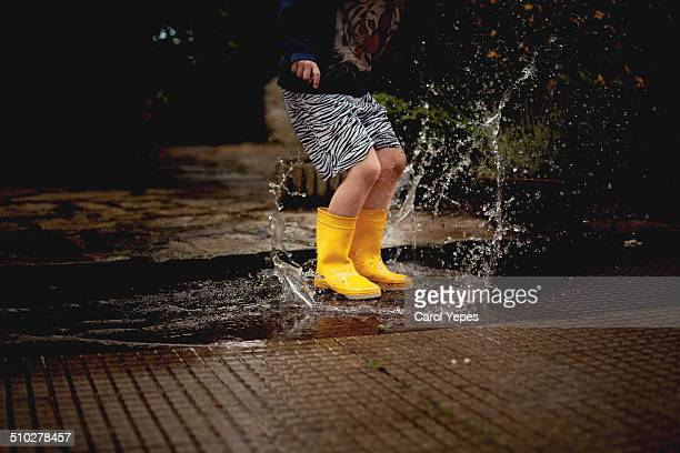 Boy splashing in a puddle
