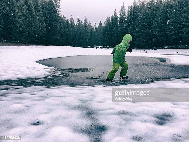 Boy splashing in icy pond