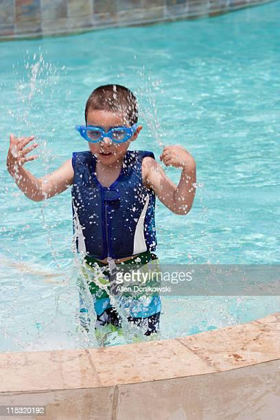 Boy splashing in pool