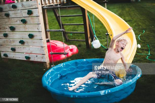 Boy splashing into a kiddie pool from a slide
