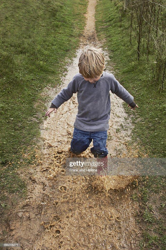 Boy splashing through muddy puddle : Stock Photo