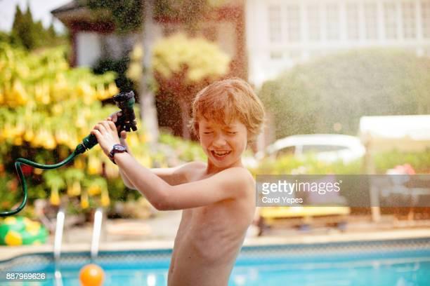 boy (9) splashing water from hose in backyard