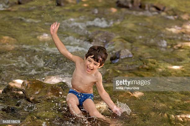 Boy splashing water in river