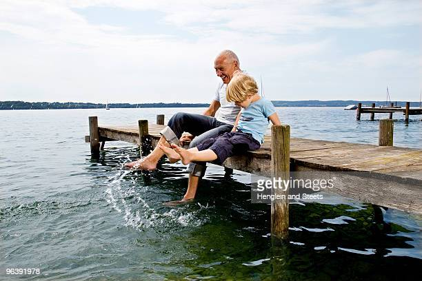 boy splashing with grandfather at lake - senior stock-fotos und bilder