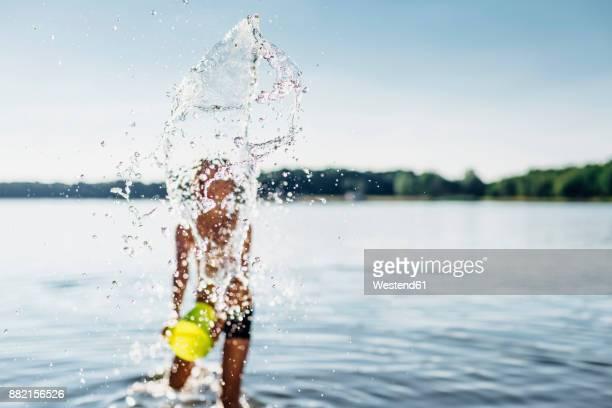 Boy splashing with water at lakeshore, close-up