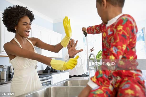 boy spraying parents - stay at home father stock-fotos und bilder