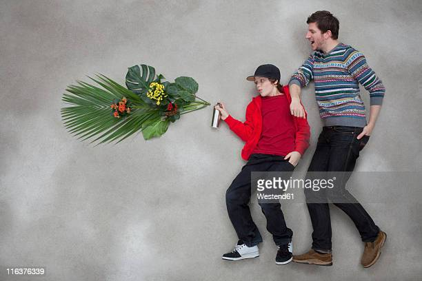 Boy spraying plant through spray can