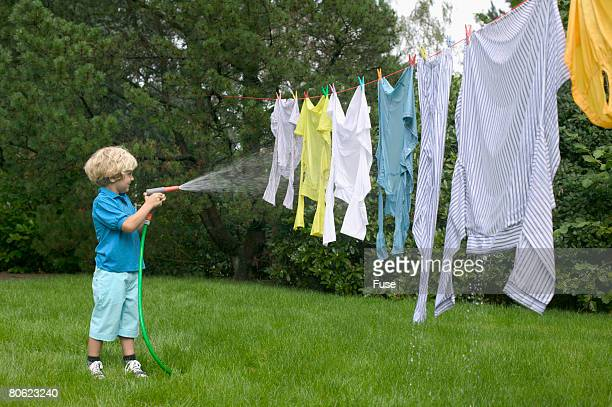Boy Spraying Water on Clothes Hanging on Clothesline