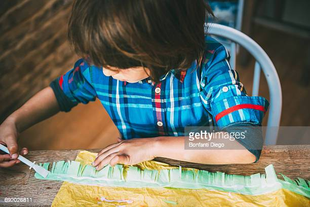 Boy spreading glue on crepe paper to make pinata