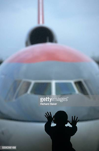 A boy spreads his hands and fingers out on a Gatwick South Terminal window Outside is the nose of an American Northwest Airlines DC10 with its third...