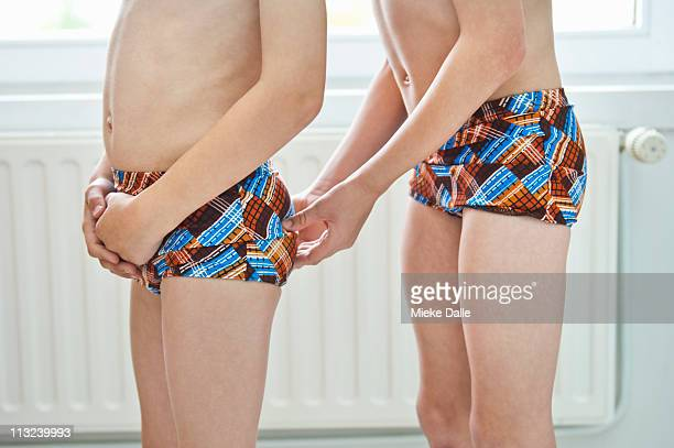 boy squeezing his brothers bottom - zwembroek stockfoto's en -beelden