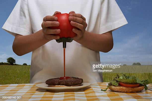 Boy (8-10) squirting Ketchup on hamburger, outdoors, mid section (Digital Composite)